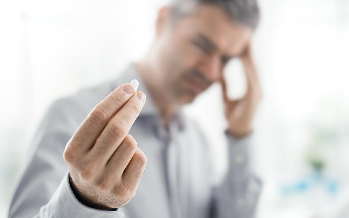 Man holding aspirin causing Tinnitus
