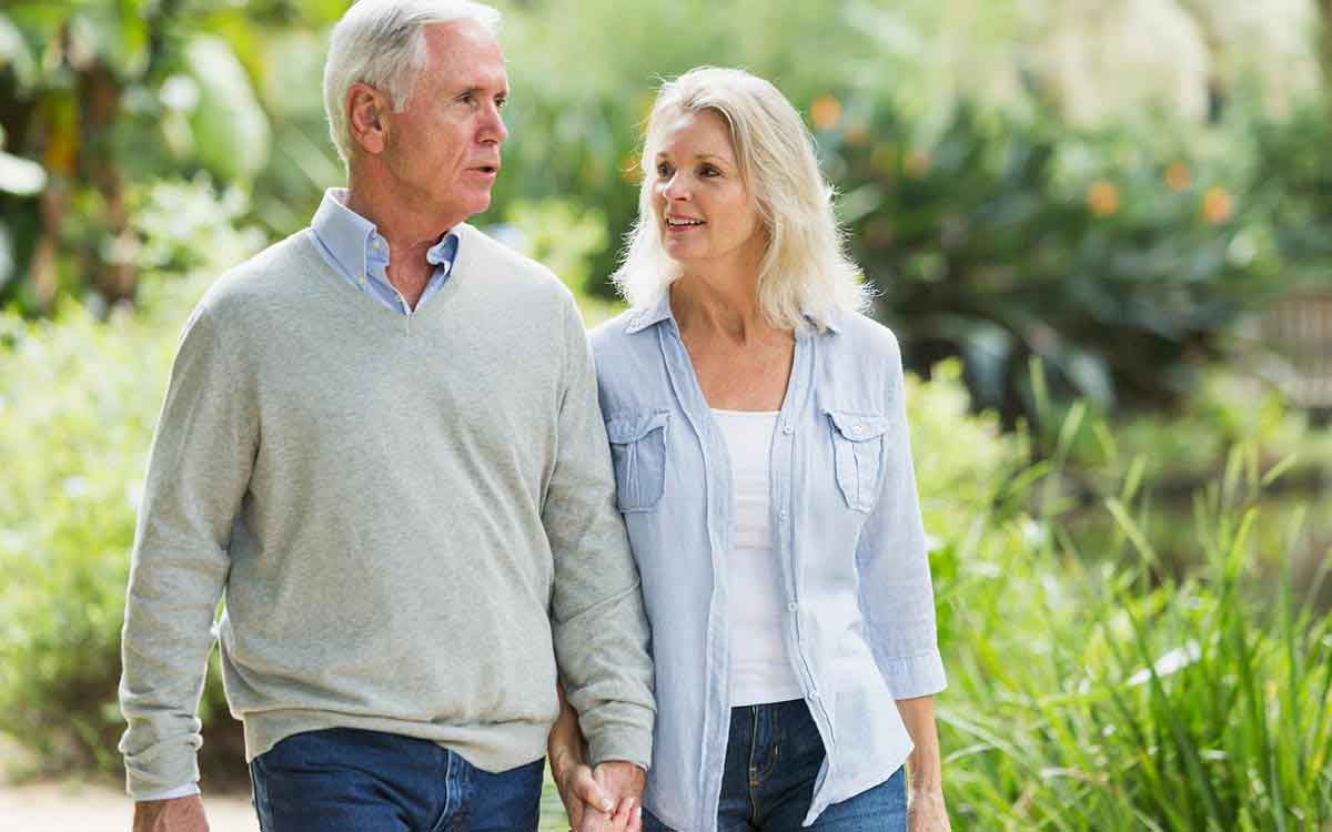 Middle aged couple walking and wondering if they should wear their hearing aid.