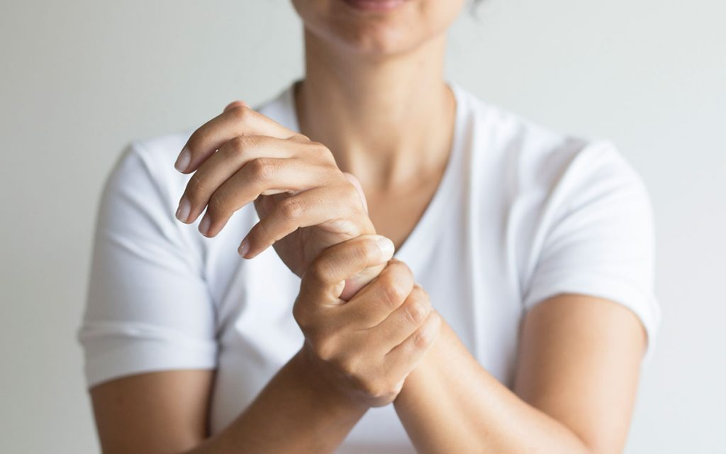 Woman holding her wrist becasue of inflammation. Hearing loss can come from inflammation.