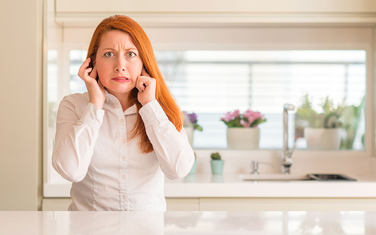 Woman holding her head unable to determine whether it's hyperacusis or misophonia.
