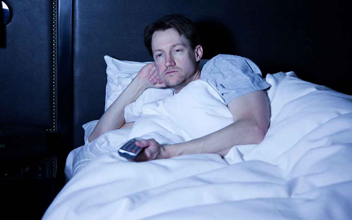 Man with insomnia from ringing in his ears watching TV all night.