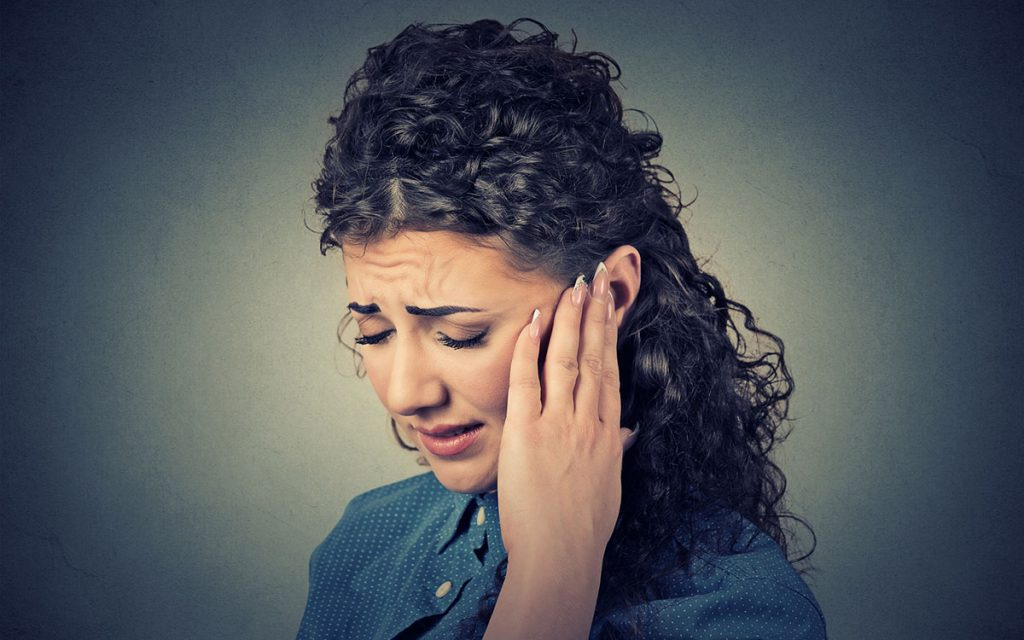 Woman holding her ear suffering from Pulsatile Tinnitus.