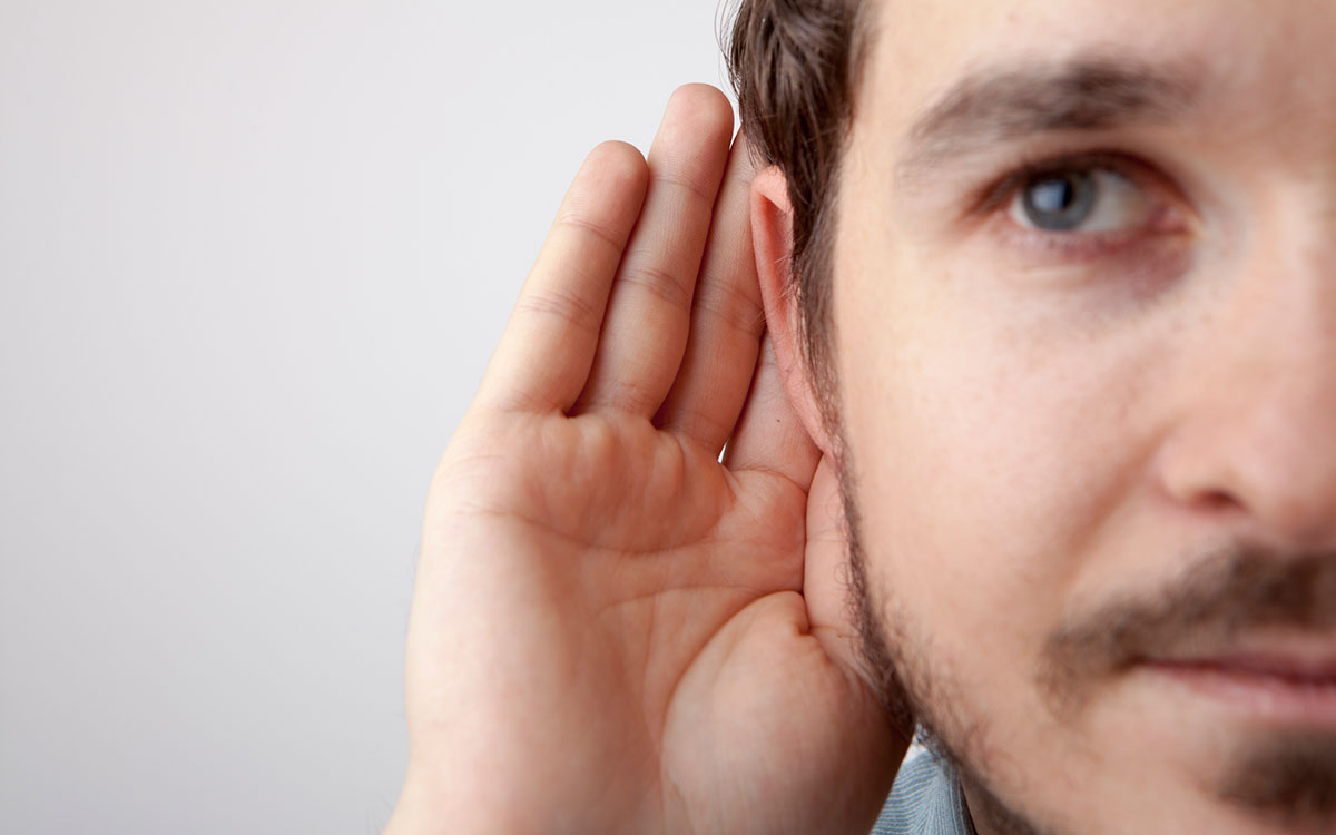 Man with hand to ear discovering many causes of hearing loss.