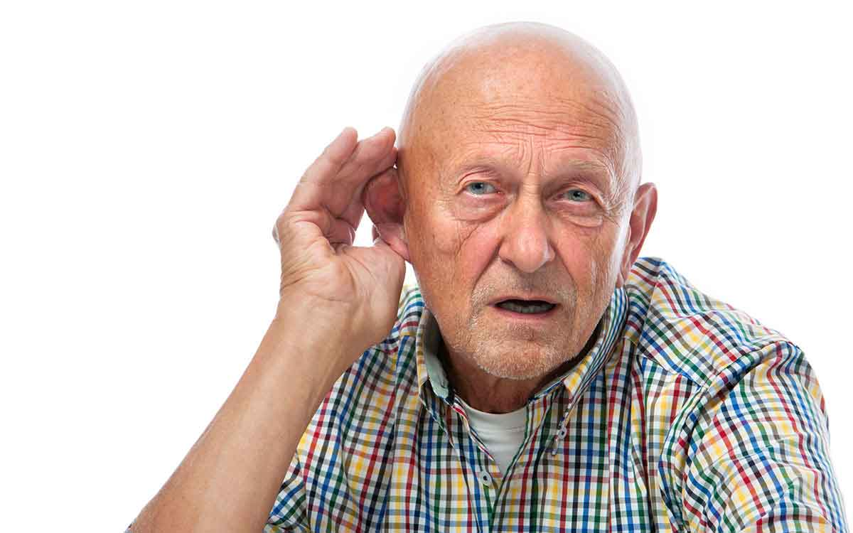 Man with hand to his ear with dangerous untreated hearing loss.
