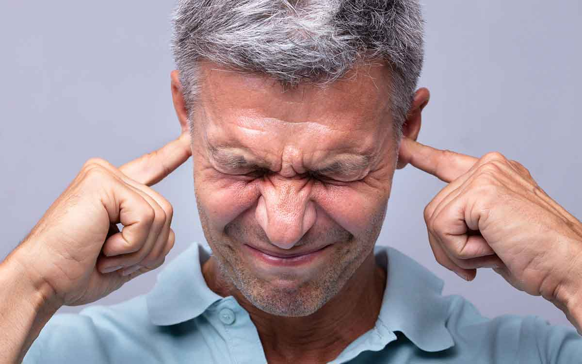 Man with his fingers in his ears blocked and causing hearing loss.
