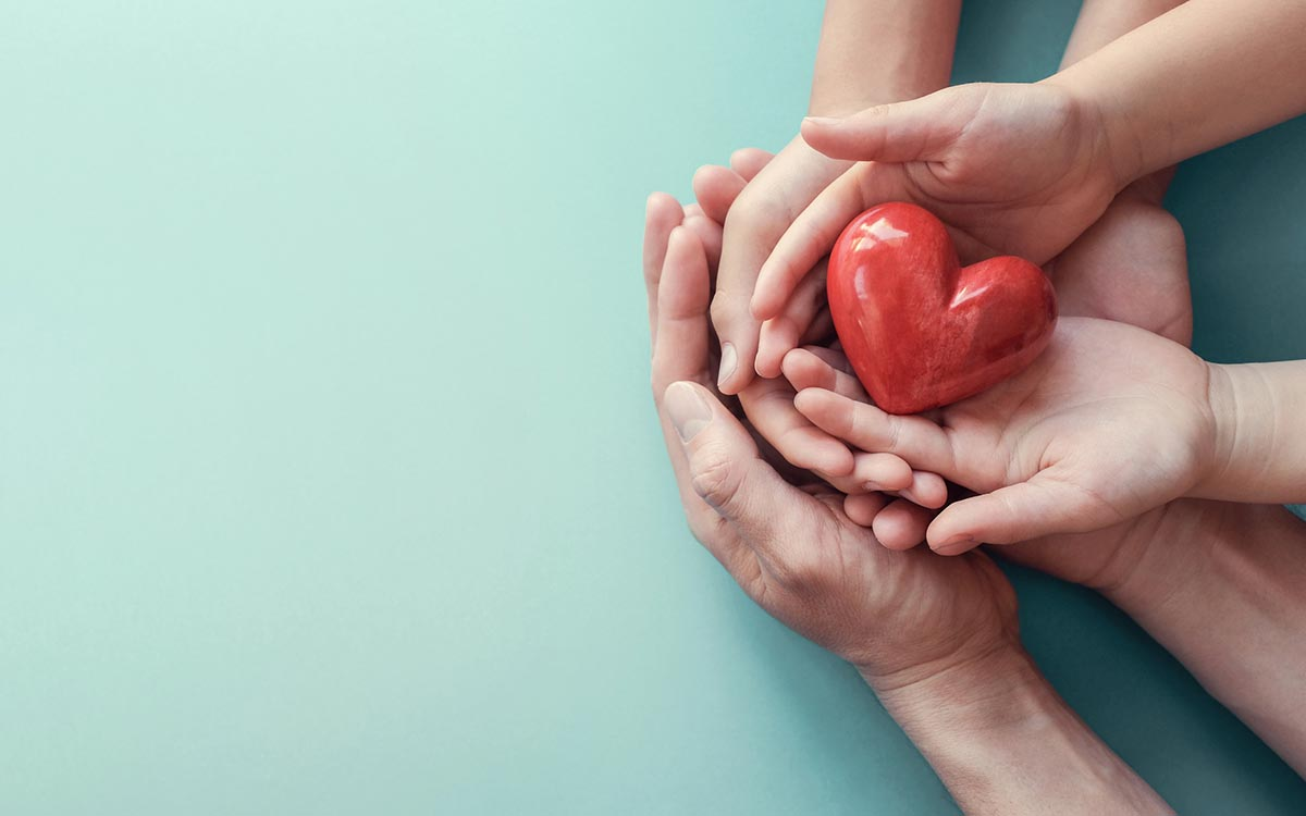 Hands holding a heart representing donating hearing aids.