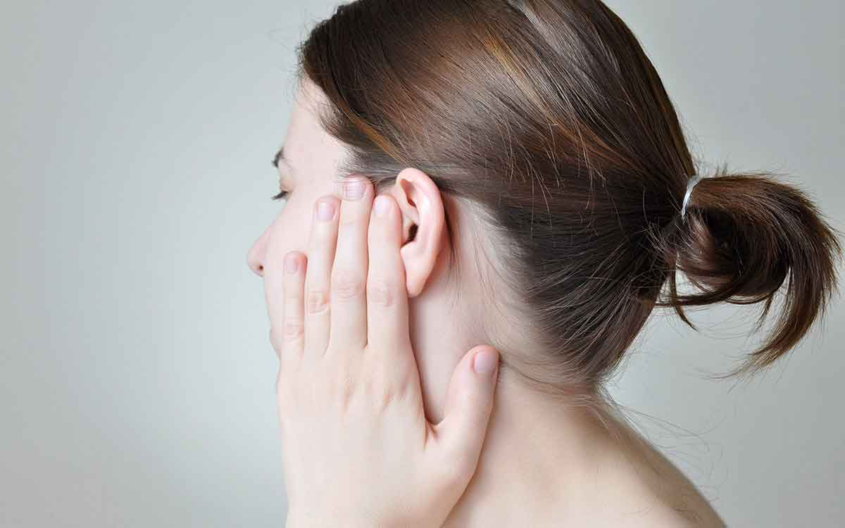 Woman with hand over her ear suffering from Tinnitus.