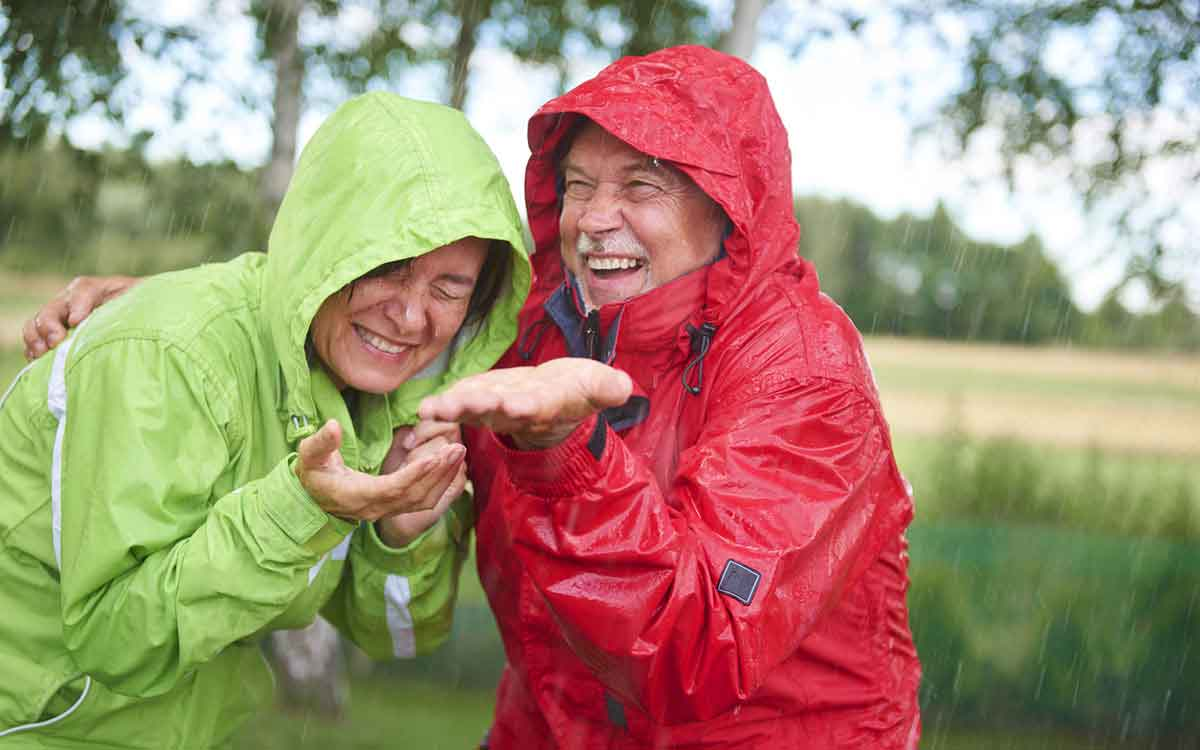 Senior couple in the rain wondering if their hearing aids can get wet.