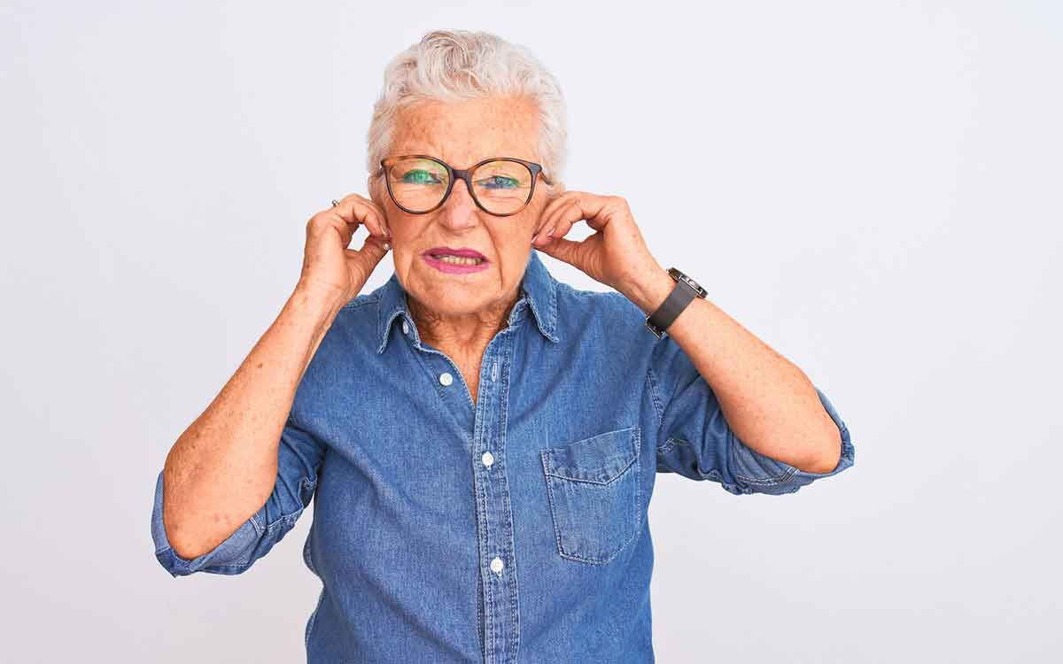 Woman with fingers in her ears suffering from Tinnitus.