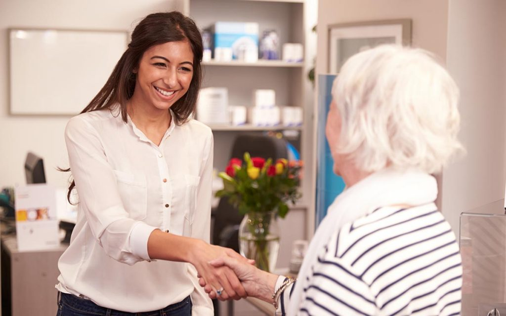 A female Audiologist greeting an elderly woman in the office for a hearing aid fitting.