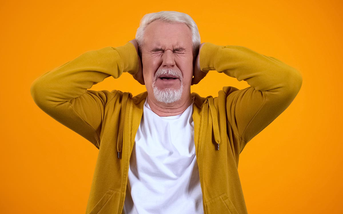 Senior man with his hands over his ears because of Tinnitus.