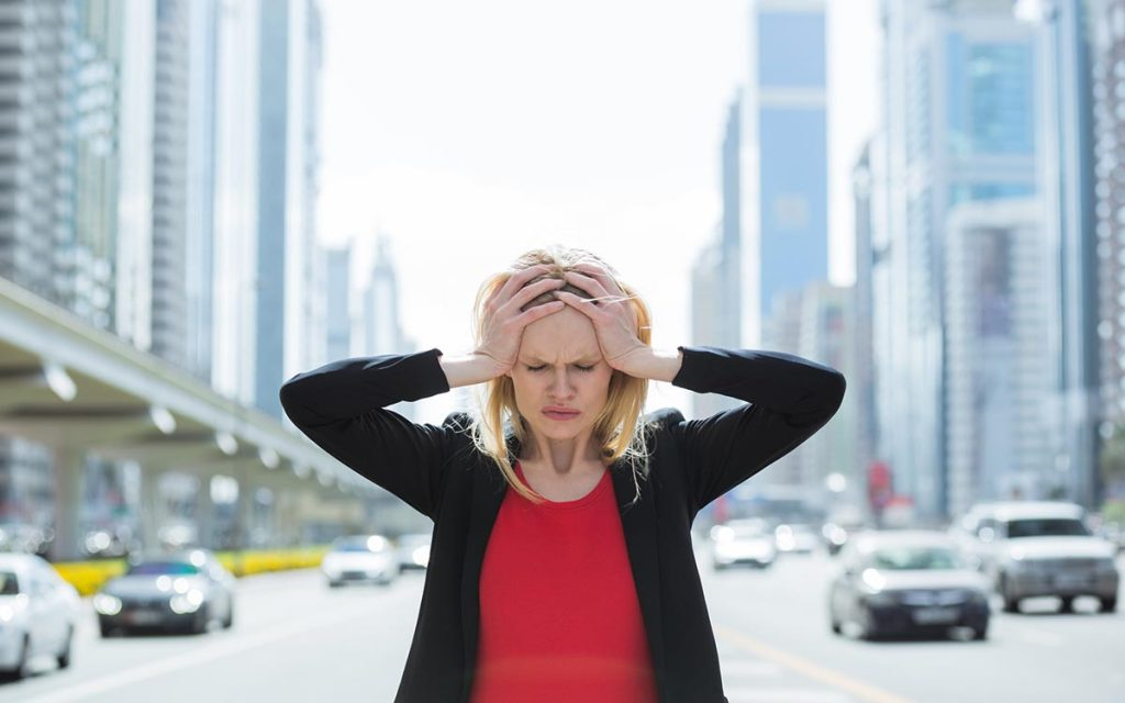 Stressed business woman in the busy city experiencing hearing loss.