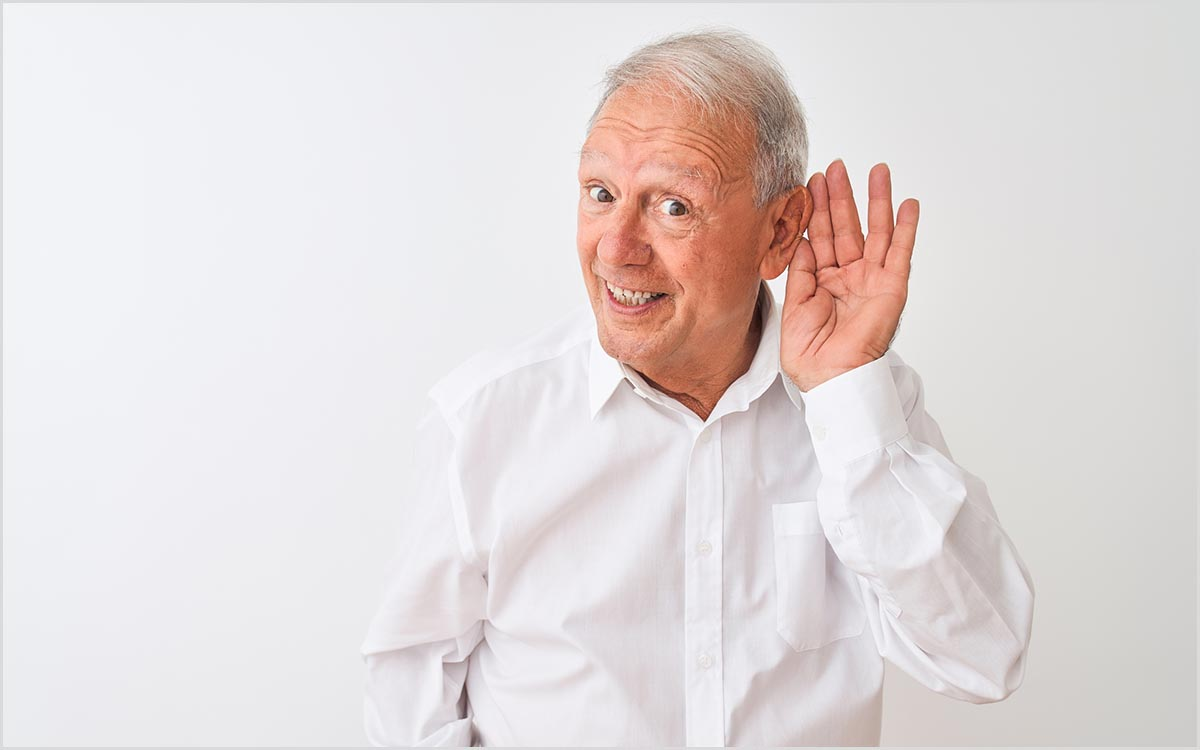 Man with his hand up to his ear. Happy about the possibility of reversing hearing loss.
