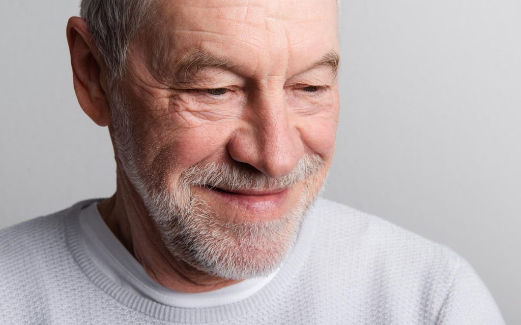 Portrait of a happy senior man with beard and mustache in a studio who is preventing aging with hearing aids.