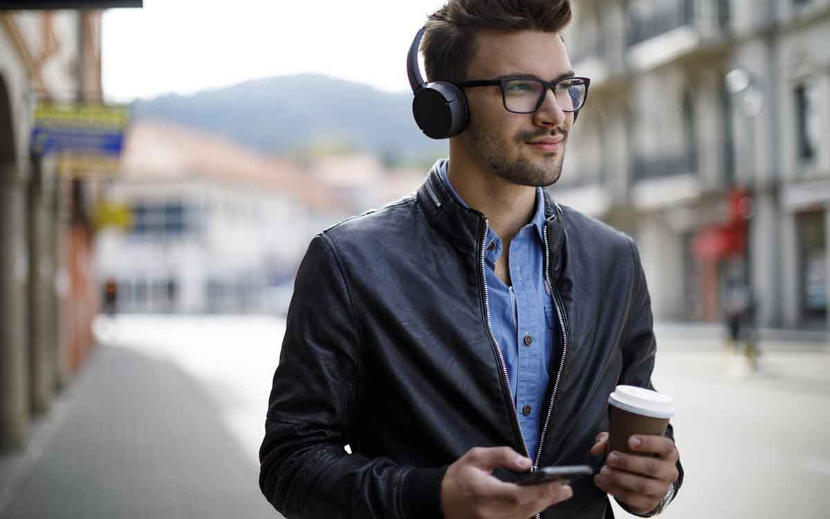 Smiling young man listening to music and drinking coffee outdoors listing to his headphones.
