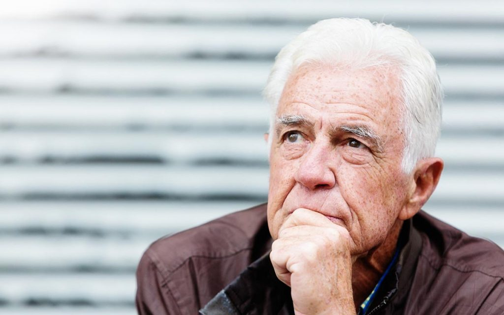 Thoughtful senior man looks serious as he contemplates life suffering from hearing loss and isolation.