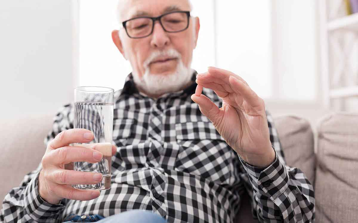 Senior man having a glass of water and pills in hand for Tinnitus.