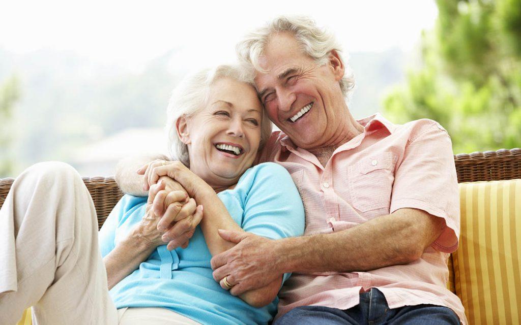 Happy senior couple avoiding the negative stigma by wearing hearing aids.