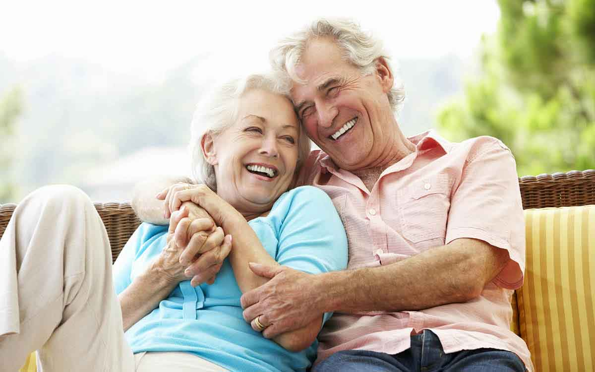Happy senior couple avoiding the negative stigma by wearing hearing aids.