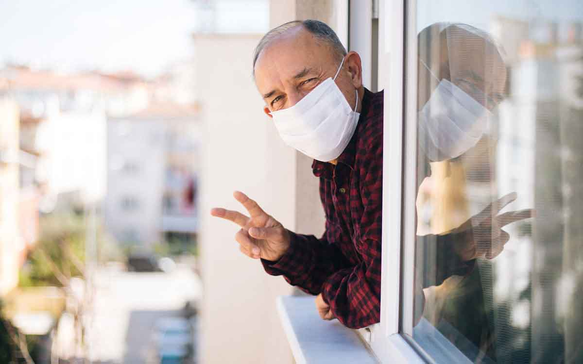 Senior man in medical mask on window breathing fresh air from quarantine not losing his hearing aids from face mask.