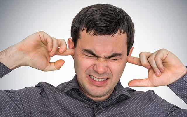 Man closes ears with fingers because of Tinnitus.