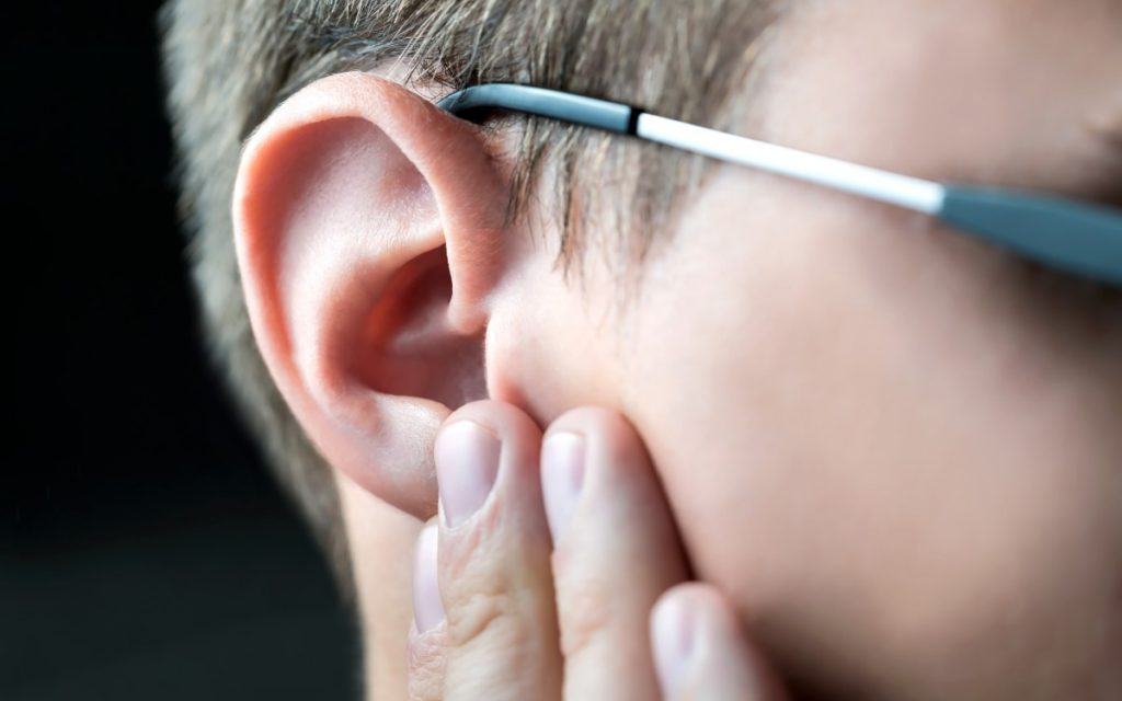 Man holding his ear suffering from otosclerosis.
