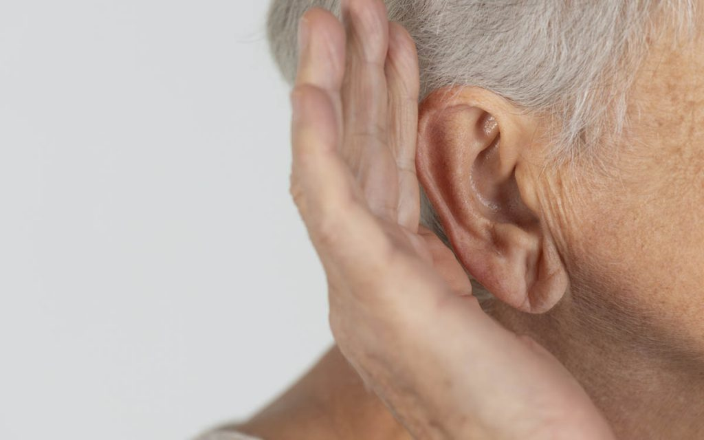 Woman with hand up to ear suffering from singe sided deafness.