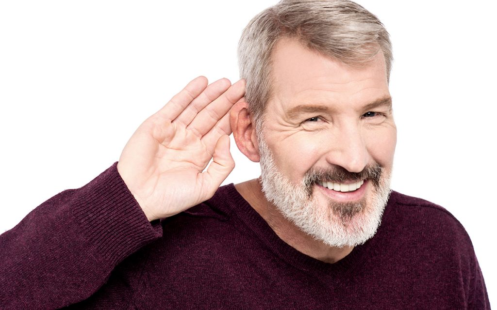 Man with hands to ear becasue of subtle signs of hearing loss.