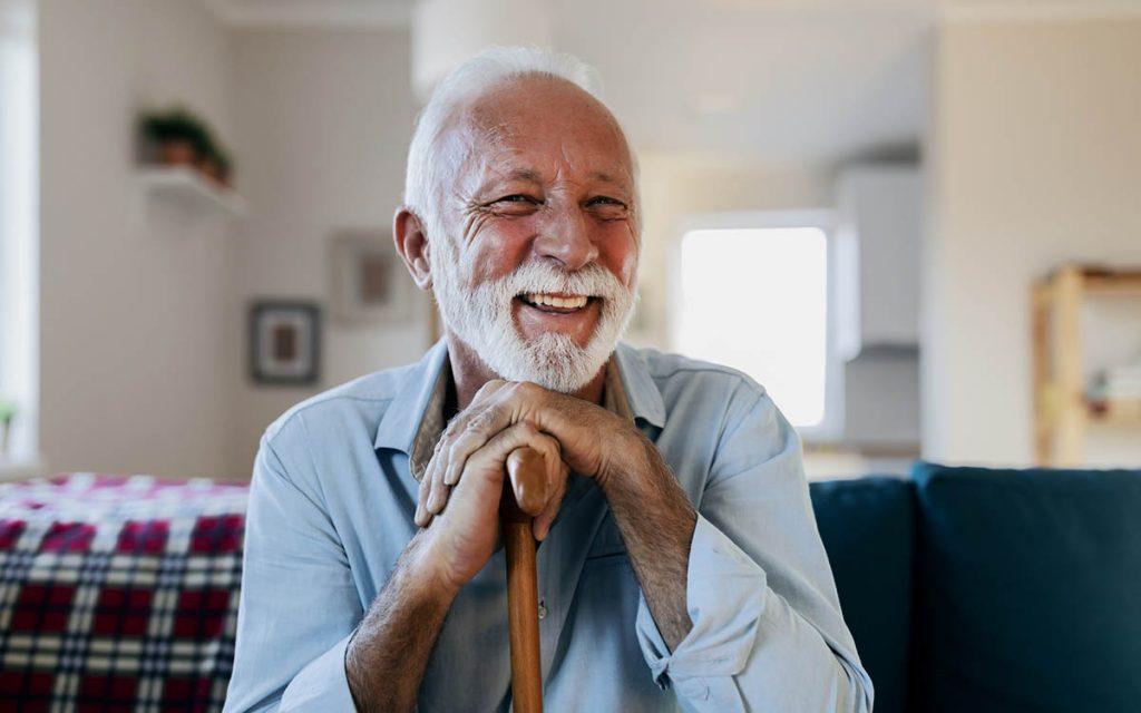 Happy senior man who has upgraded his hearing aid.