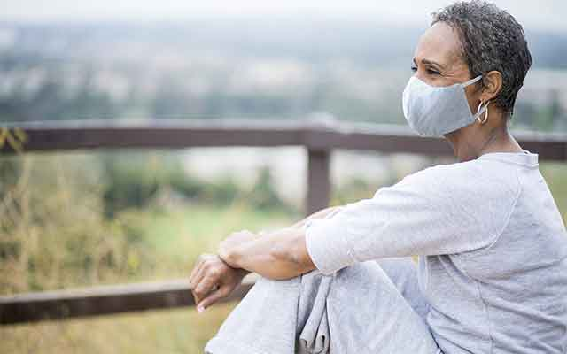 Woman with mask on contemplating hearing loss.